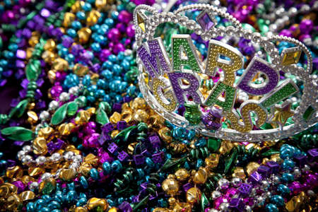 A colorful mardi gras crown or tiara lying on top of beads, holiday theme photo