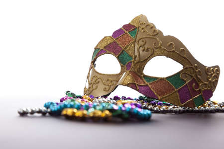 lint: A group of mardi gras beads an mask with copy space
