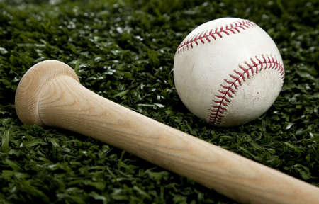 An end of a wooden baseball bat and a white baseball on green grass Stock Photo - 5230460