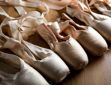 ballet shoes: A group or background of used ballet pointe shoes or slippers on a wooden floor Stock Photo