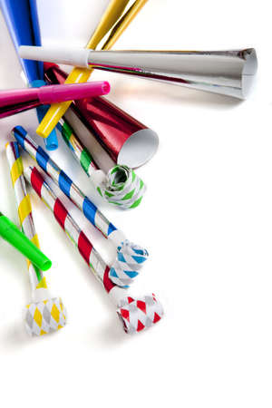 noise maker: A group of colorful party noise makers, including horns etc. , on a white background with copy space