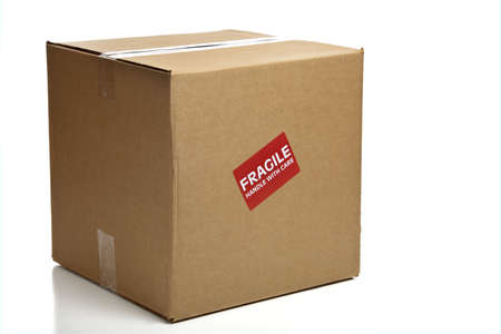 handle with care: A blank, brown, corrugated cardboard box or shipping box with a Fragile - Handle with Care sticker on a white background
