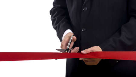 A man in a business suit cutting a red silk ribbon with shiny scissors, grand opening or beginning concept photo