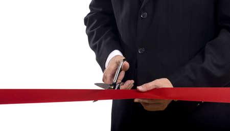 taglio del nastro: Un uomo in un tailleur di taglio un nastro di seta rossa con le forbici lucido, grande apertura o all'inizio concetto Archivio Fotografico