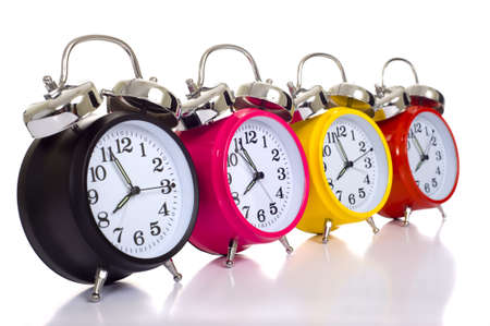clocks: A row of colorful alarm clocks on a white background with copy space.  Time concept Stock Photo