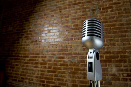 old items: A vintage looking microphone in front of an old brick wall with copy space