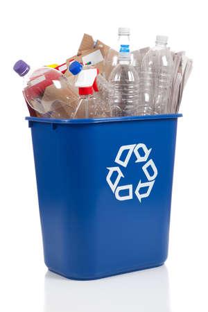 envases plasticos: Un desbordamiento azul papelera de reciclaje llena de botellas de pl�stico, peri�dicos y cajas, con el s�mbolo recyle en la parte delantera Foto de archivo
