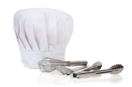 A chefs kitchen tools including spoons, wisk, tongs and a toque or hat on a white background with copy space