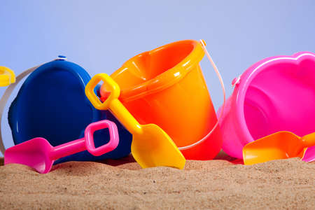 a row of colorful beach buckets or pails with shovels on a sandy beach with blue sky background with copy space Stock Photo - 5391050
