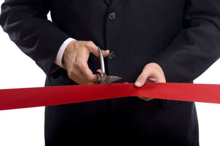 A man in a business suit cutting a red silk ribbon with shiny scissors, grand opening or beginning concept Stock Photo - 5391036