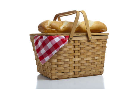 basket: A wicker picnic basket with a red gingham cloth and bread on a white background Stock Photo