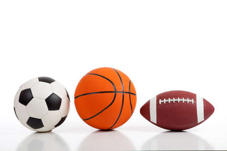 Assorted sports equipment on white including a basketball, a soccer ball, and an American Football