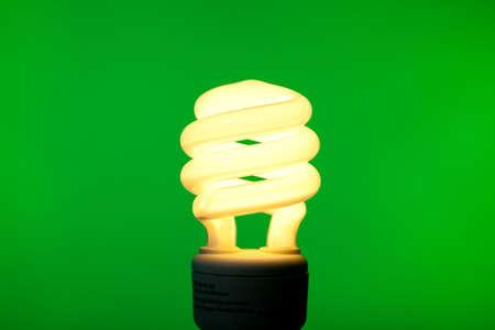 A compact flourescent bulb on a green background - energy saving, environmental theme photo