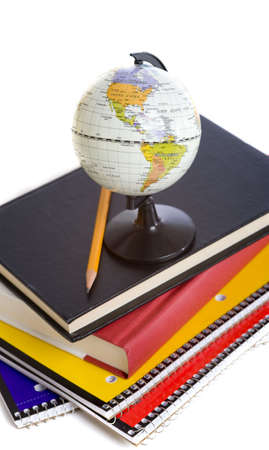 objects: A stack of school books and a miniature globe on a white background with a pencil