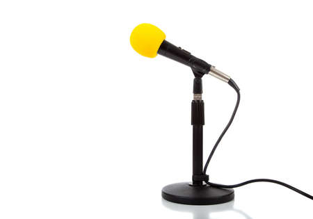 a modern speakers microphone with a yellow wind guard on a white background with copy space Stock Photo - 5409938