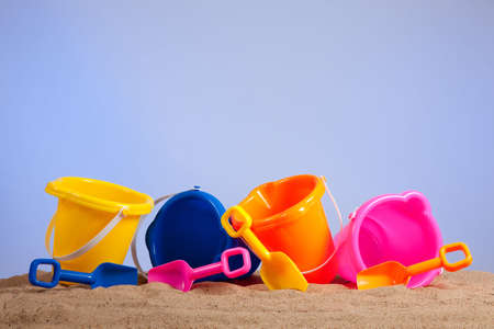 a row of colorful beach buckets or pails with shovels on a sandy beach with blue sky background with copy space