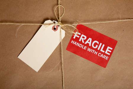 manejar: Un cuadro de color marr�n de env�o con una etiqueta en blanco y una pegatina fr�gil con espacio de copia  Foto de archivo
