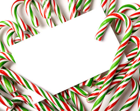 notecard: A white notecard, greeting card, or invitation surrounded by brightly color Christmas Candy Canes with copy space