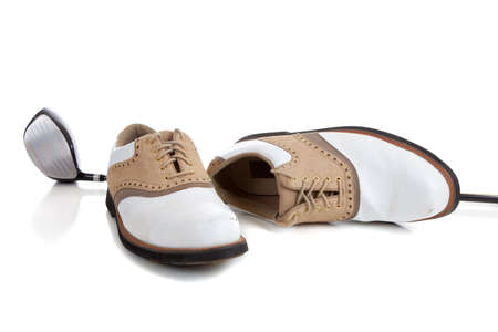 A pair of golfing shoes and a golf club on a white background with copy space