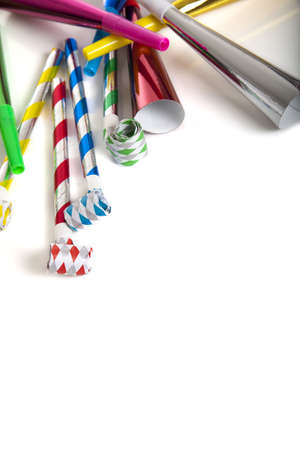 A group of colorful party noise makers, including horns etc. , on a white background with copy space photo