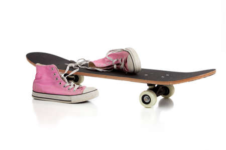 A skate board and pink sneakers on a white background with copy space photo