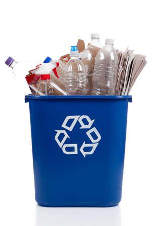 reciclable: Un desbordamiento azul papelera de reciclaje llena de botellas de pl�stico, peri�dicos y cajas, con el s�mbolo recyle en la parte delantera Foto de archivo