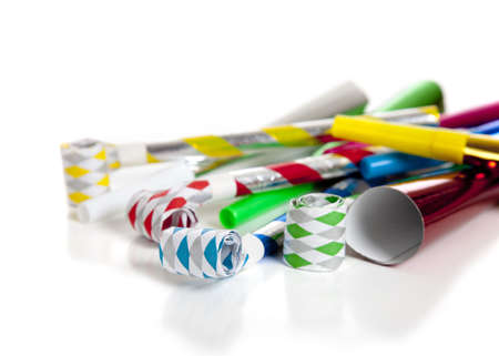 A group of colorful party noise makers, including horns etc. , on a white background with copy space