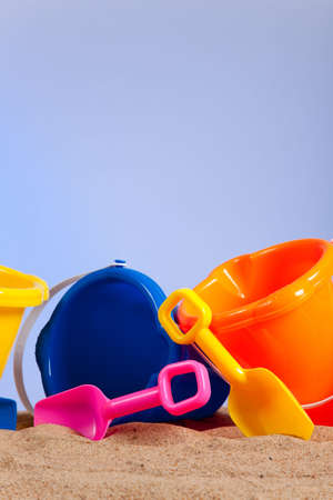 a row of colorful beach buckets or pails with shovels on a sandy beach with blue sky background with copy space Stock Photo - 5452058