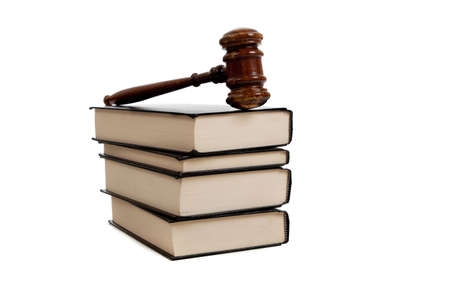 A stack of legal books and a wooden gavel on a white background photo