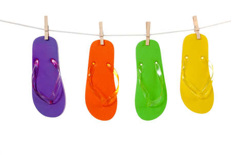 accessorize: A group of colorful flip-flop sandles hanging by clips from a clothes line