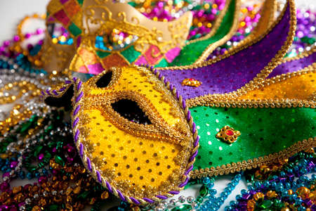 A group of two mardi gras mask and beads