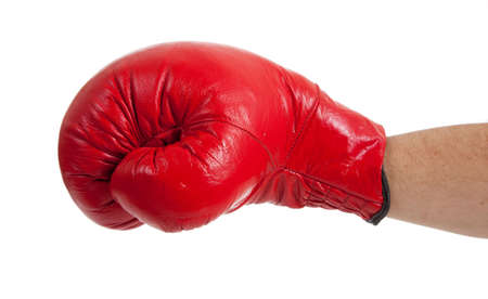 A close-up of a persons arm throwing a punch with a red boxing glove on a white background