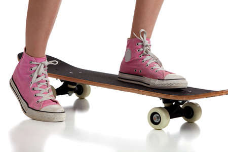 A young girl on a skateboard with pink sneakers on a white background photo