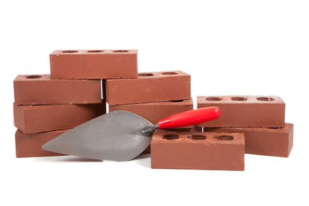 A stack of red bricks on a white background with a pointing trowel Stock Photo - 5497232