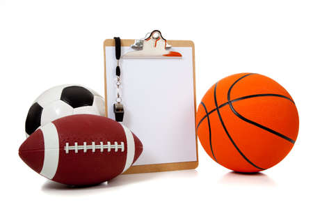 A group of sports ball with a blank clipboard including a basketball an American football and a soccerball on white photo