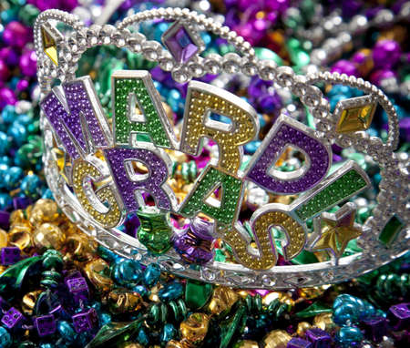 A colorful Mardi Gras crown on top of a group of colorful beads photo