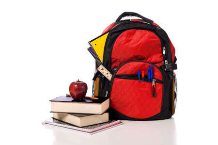 school bag: Colorful school back pack overflowing with school supplies including pens, pencils. tablets, notebooks, and books Stock Photo