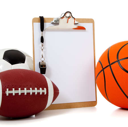 A group of sports ball with a blank clipboard including a basketball an American football and a soccerball on white