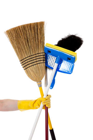 A gloved yellow hand holding a broom, a mop and a duster - household chores theme Stock Photo