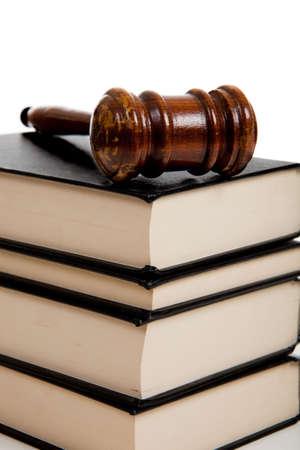 Een houten hamer rechters boven op een stapel wetboeken op witte achtergrond