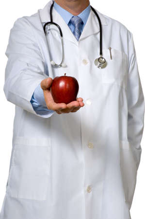 A doctor dressed in a white lab coat offering and apple - healthy eathin concept photo