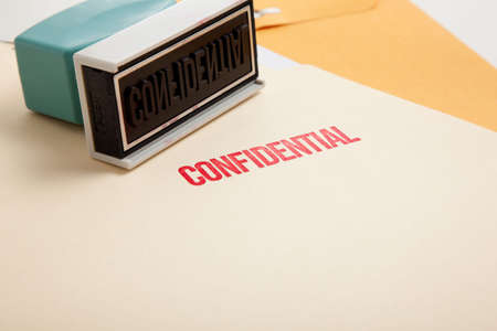 A stamp with the word confidential on a stack of folders with copy space photo