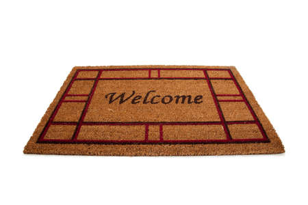 A mat or carpet with the word Welcome printed on it.  Hospitality Stock Photo