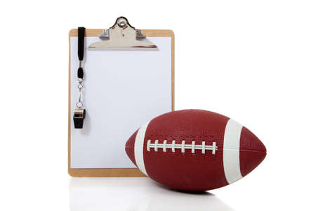 whistling: A football coaches clipboard with a whistle and an American football on a white background