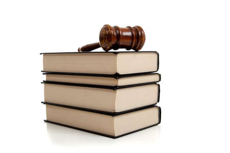 A wooden judges gavel on top of a stack of law books on white background