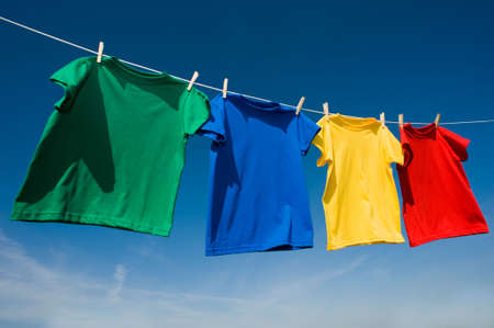A group of primary colored t-shirts ona clothesline in front of blue sky