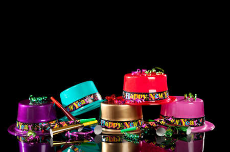 one year: Colorful New Years Eve party hats on a black background