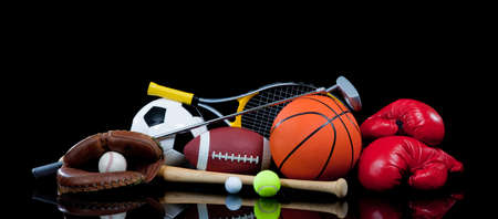 A group of sports equipment on black background including tennis, basketball, baseball, american fotball and soccer and boxing equipment on a black background with copy space Stock Photo - 5618848