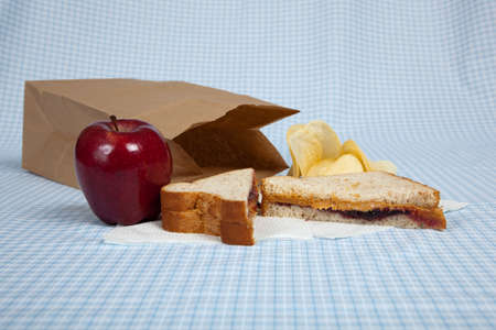 apple sack: A students sack lunch with a peanut butter and jelly sandwich, potato chips and an apple