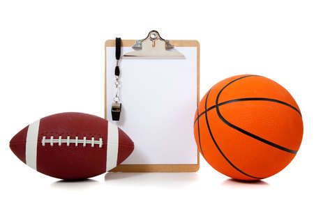 a basketball and American football with coachs clipboard with whistle and white copy space photo